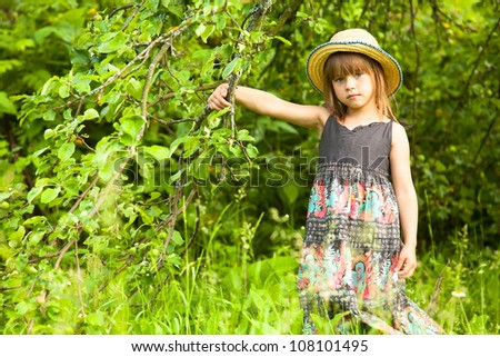 Little beautiful girl posing in a straw hat in the park. - stock photo