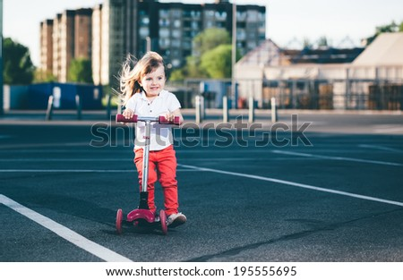 Little beautiful girl riding a scooter - stock photo