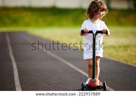little beautiful girl riding scooter at stadium - stock photo