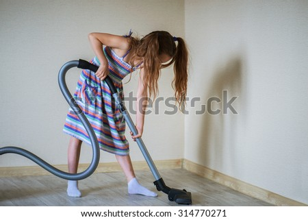 Little beautiful girl running with vacuum cleaner at home. - stock photo