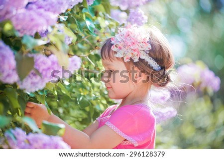Little beautiful  girl standing in the lilac park on a sunny morning and smiling. - stock photo