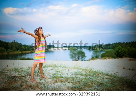 Little beautiful girl standing on the sand near the lake. - stock photo