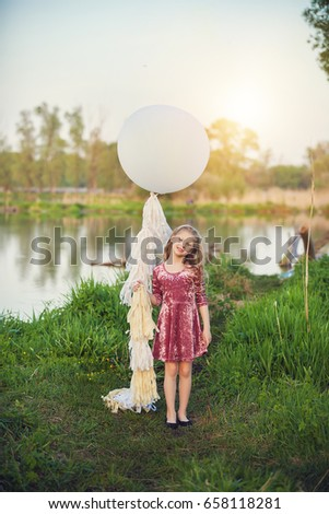 Little beautiful girl with big balloon near the lake at sunset