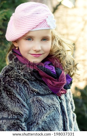 little beautiful girl with blue eyes in pink hat standing on the street