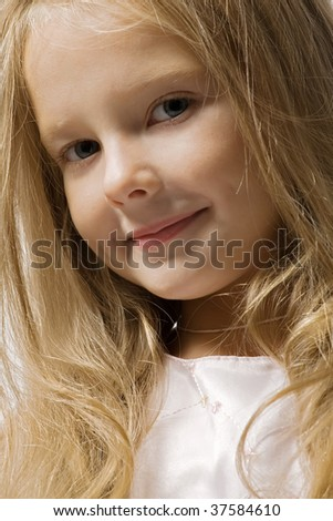 Little beautiful girl with long hair smiles and looks in the camera