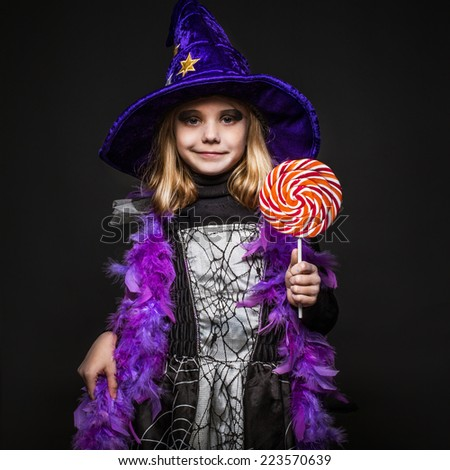 Little beautiful halloween witch with colorful candy. Studio portrait over black background  - stock photo