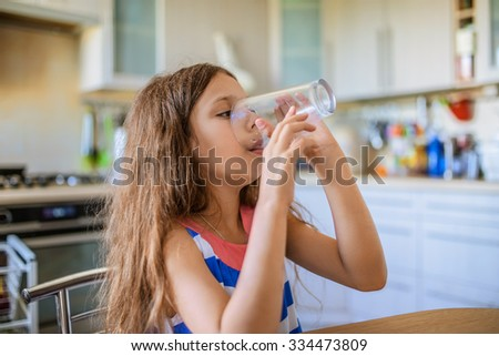 Little beautiful happy girl drinking a glass of water in the kitchen. - stock photo