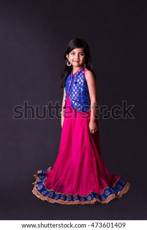 Little beautiful Indian girl looking up over black background, isolated