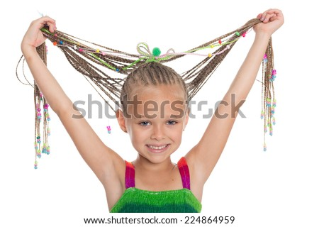 Little beautiful playful girl holding hands her dreadlocks. Girl is six years old.  - stock photo