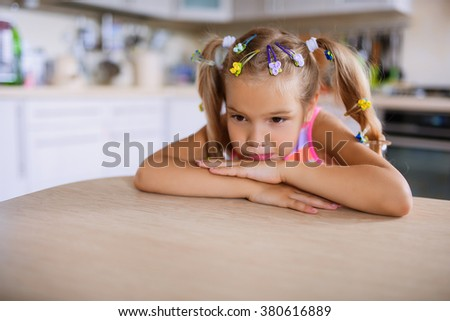 Little beautiful sad girl sits at a table in the kitchen.