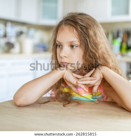 Little beautiful sad girl sitting at kitchen table and think. - stock photo