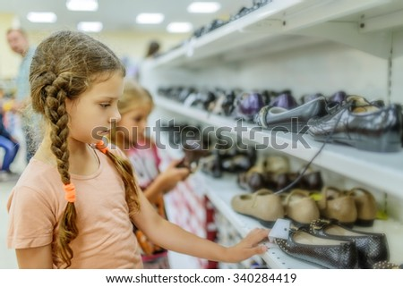 Little beautiful sisters chooses shoes at a store. - stock photo