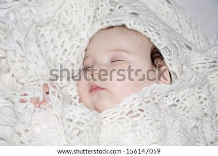 Little beautiful sleeping baby lies on white sheet in knitted shawls on bed. - stock photo