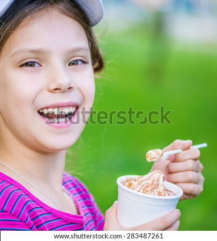 Little beautiful smiling girl holding an ice cream on background summer park. - stock photo