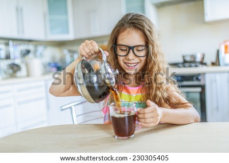 Little beautiful smiling girl in glasses pours tea from teapot into cup at kitchen table. - stock photo