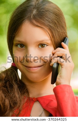 Little beautiful smiling girl in red dress talking on cell phone, against green summer park. - stock photo