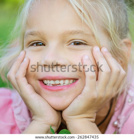 Little beautiful smiling girl lies on green grass, summer in city park. - stock photo