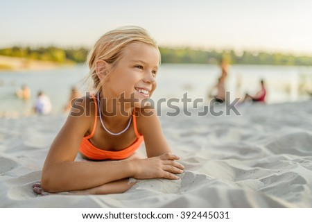 Little beautiful smiling girl lying on the sand at the beach.