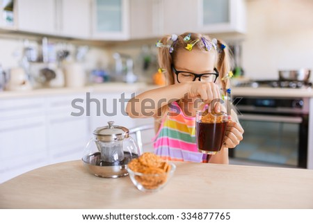 Little beautiful smiling girl pours tea from teapot into cup at kitchen table. - stock photo