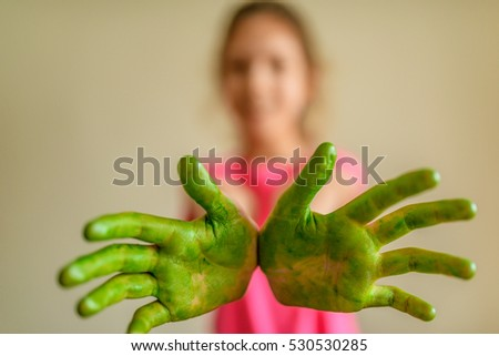 Little beautiful smiling girl shows hands that painted green paint.