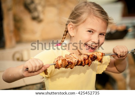 Little beautiful smiling girl  with pleasure eats  kebab outdoor at the day time. Concept of healthy life.