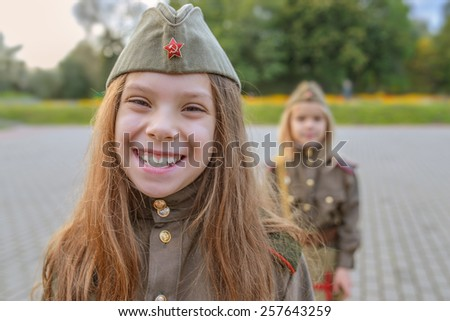 Little beautiful smiling girls in Soviet military uniforms. - stock photo