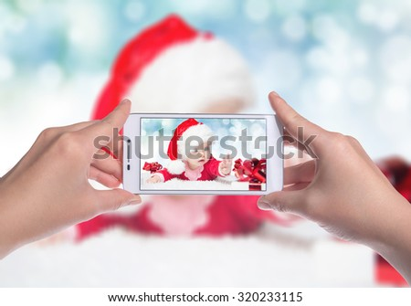 Little beautiful young girl dressed as Santa Claus with a gift in their hands. New Year's holidays. Mobile photo. Mobile Technologies - stock photo