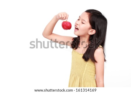 Little beauty girl eating red apple on white background