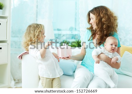 Little beauty giving a present to her mom and wishing a happy birthday - stock photo