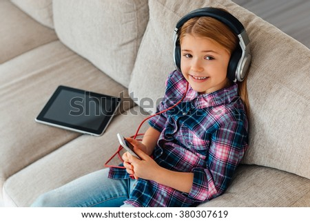 Little beauty listening music. High angle view of cheerful little girl in headphones holding smart phone and looking at camera with smile while sitting on the couch at home - stock photo