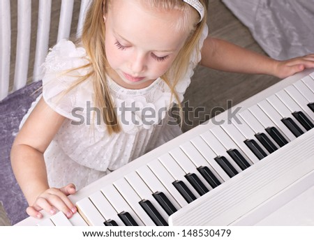 little beauty well-dressed girl  playing on white piano, top view - stock photo