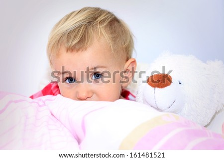 Little best friends. Cute baby girl with teddy bear smiling and looking at camera - stock photo