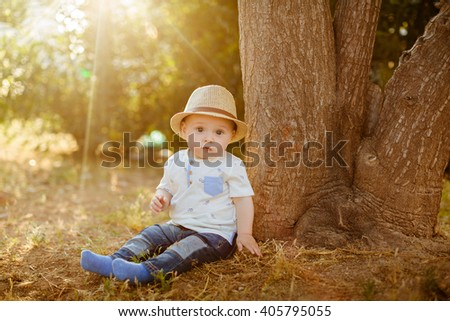Little big-eyed boy in a hat sits near the tree at sunset in the summer - stock photo