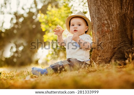 Little big-eyed little boy in a hat sits near the tree at sunset in the summer and holding a straw - stock photo