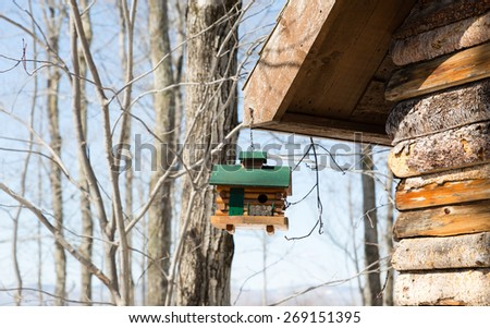 Little bird house hanging from the rooftop of a house - stock photo