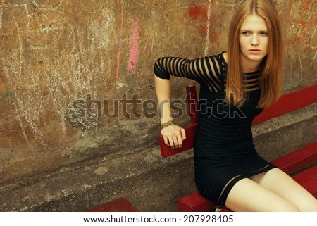 Little black dress concept. Portrait of beautiful fashionable woman in black cocktail dress sitting on red bench in old italian yard. Drawings on wall. Vintage style. Copy-space. Outdoor shot - stock photo