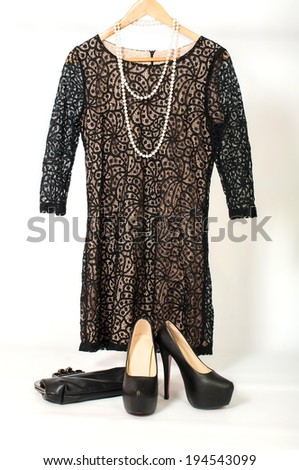 little black dress hanging on a hanger and shoes on high heels - stock photo