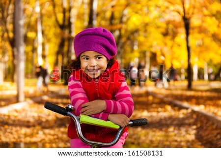 Little black 3 years old black girl riding a bicycle in the park resting on stern - stock photo