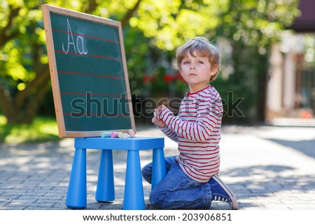 Little blond boy at blackboard practicing writing letters, outdoor school. Back to school concept - stock photo