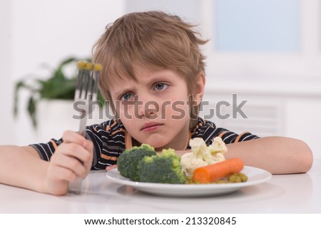 little blond boy eating at kitchen. unhappy child sitting at breakfast and looking at fork - stock photo