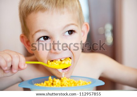 Little blond boy eating corn flakes with milk - stock photo