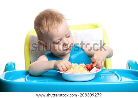 Little blond boy eating spaghetti  - stock photo