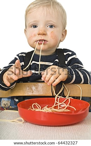 Little blond boy eating spaghetti