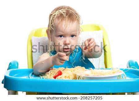 Little blond boy eating spaghetti, with pasta on his head - stock photo