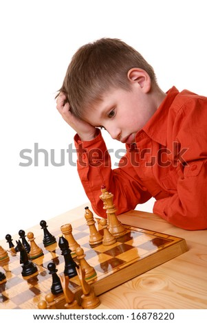 Little blond boy in orange shirt thinking deep while playing chess game - stock photo