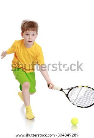 Little blond boy in the yellow shirt, green shorts playing tennis. The boy holds in his left hand a racket for playing tennis which he swings by-Isolated on white background - stock photo