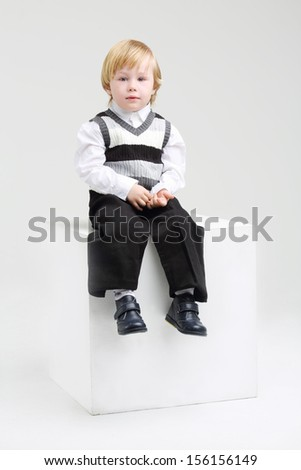 Little blond boy in vest sits on big cube and looks at camera on white background.