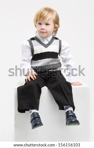 Little blond boy in vest sits on big cube and looks away on white background. - stock photo