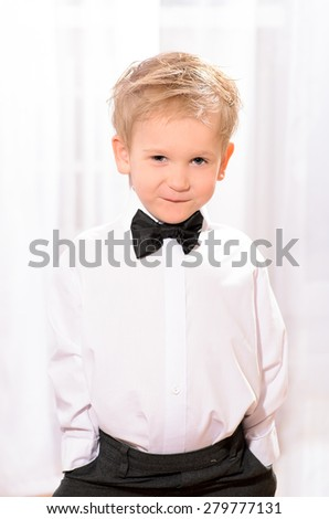 little blond boy in white shirt with black bow tie indoors
