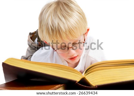 Little blond boy is reading a thick good book - stock photo